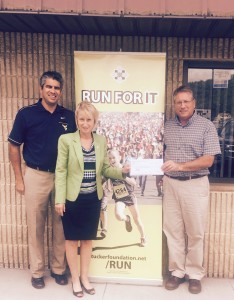 Mike Chechko and Roger Bolten (BCCF), present a check to Diane Hinkle, Development Director  for Tucker Community Foundation. The funds benefit Barbour County teams participating in Run For It.